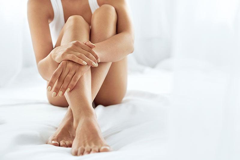 Ästhetische Dermatologie - eine junge Frau sitz mit verschränkten Beinen am Bett