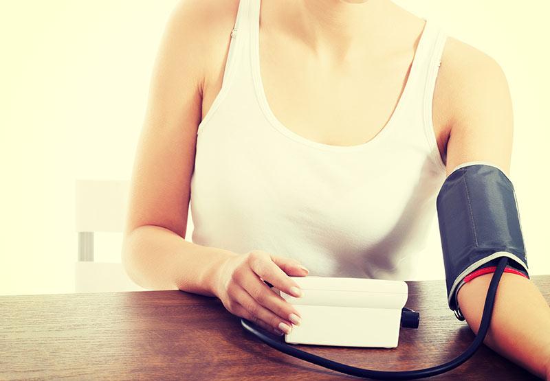 Eine Frau misst ihren Blutdruck mit einem Blutdruckmessgerät