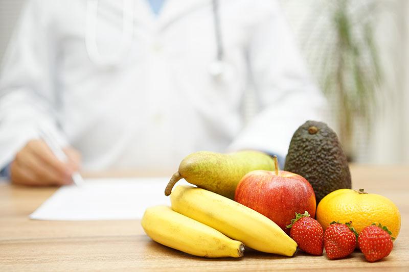 Früchte auf einem Arzttisch, Banane, Avocado, Birne, Erdbeeren, Apfel. Ein Arzt verschreibt gesunde Ernährung