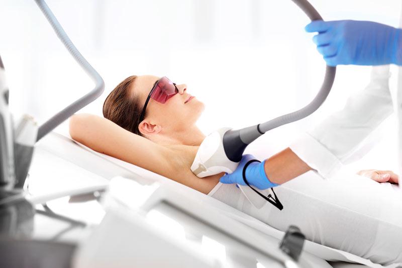 Hocheffektive Laserbehandlung zur Entfernung von Haaren. Eine Patientin liegt bei der Haarentfernungsbehandlung