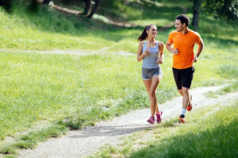 Zwei vitale Personen laufen am Waldweg entlang